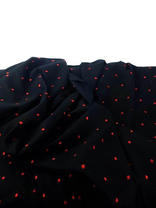 Tela negra con lunares rojos