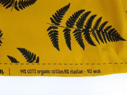 Tejido punto sudadera mostaza verdoso con hojas estampadas en algodón orgánico