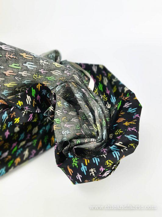 Tela de cactus multicolor con fondo negro diseño de Alexander Henry