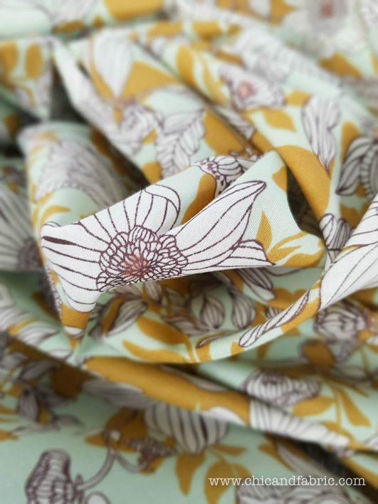 Voilé fino de algodón estampado de flores blancas sobre fondo menta