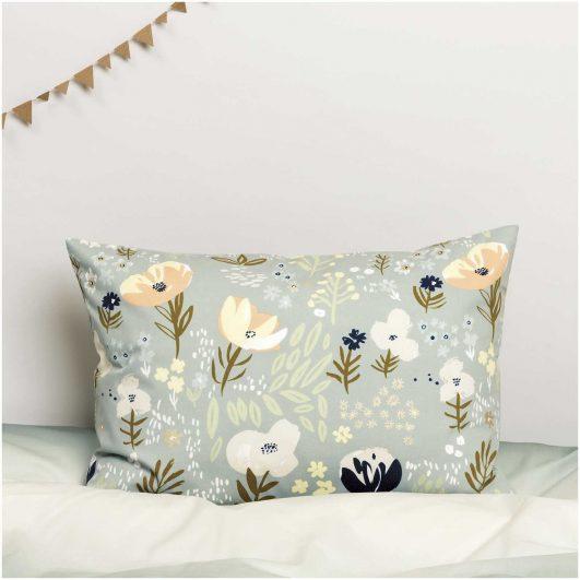 Cojín estampado con tela de flores en tonos fríos, fondo gris verdoso y detalles en dorado