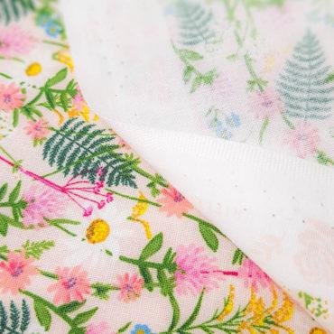 Tissu imprimé avec marguerites blanches et fougères à fond rose pâle