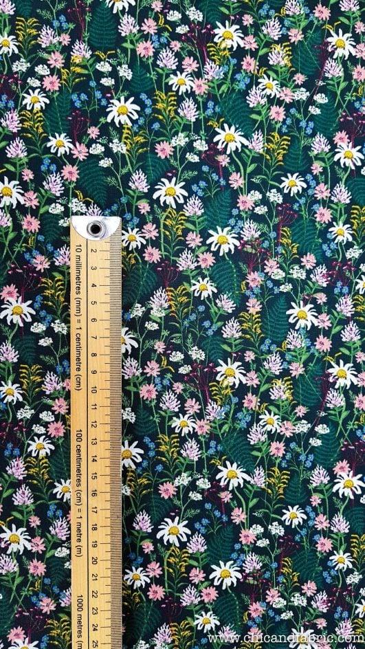 Tela de flores pequeñas, estampada de margaritas blancas y helechos con fondo oscuro