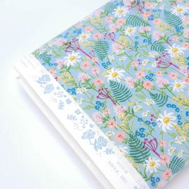 Tissu imprimé avec marguerites blanches et fougères sur fond bleu clair